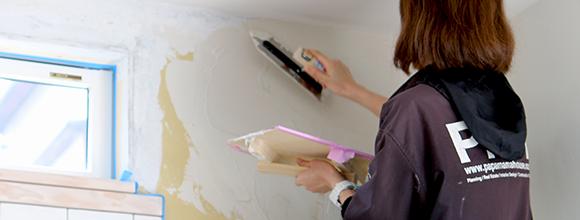 注文住宅の壁を塗っている女性