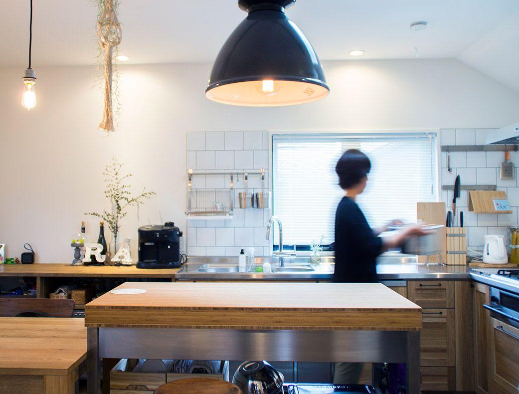 注文住宅のおしゃれなキッチンで主婦が料理