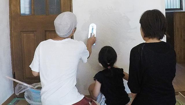 注文住宅の漆喰壁を家族で塗っている